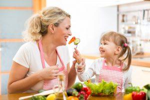 People - woman and little girl making veggies