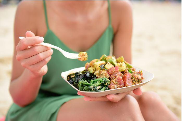 Woman eating salmon poke bowl